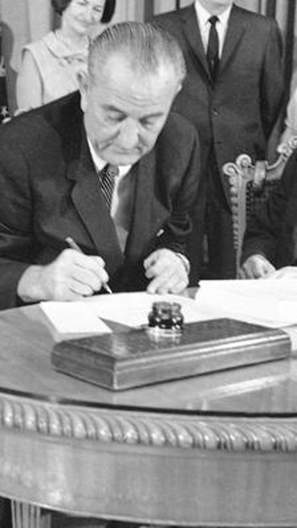 July 30, 1965 file photo, President Lyndon B. Johnson uses the last of many pens to complete the signing of the Medicare Bill into law