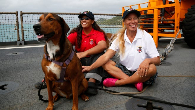 Jennifer Appel, right, and Tasha Fuiava sit with their dogs on the deck of the USS Ashland Monday, Oct. 30, 2017,  at White Beach Naval Facility in Okinawa, Japan.