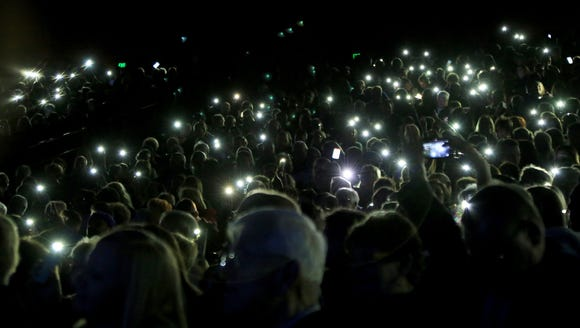 Audience members hold their illuminated cellphones