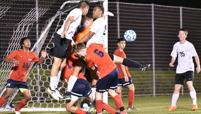 Oakland and Central Magnet players collide near the goal following a corner kick during Tuesday's game, won by the Patriots 2-0. The two teams have formed a successful rivalry in recent years.