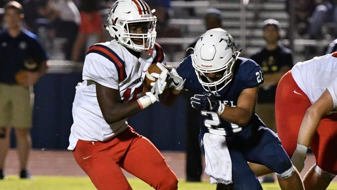 Oakland's Jeron Rooks eludes a Siegel defender en route to a six-touchdown night in the Patriots' 50-14 win.