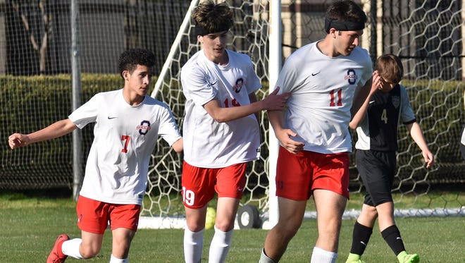 Oakland players congratulate Ben Massaro (11) after he scored the go-ahead goal Sunday in a 2-1 win over Central Magnet.