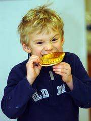 Elijah Slinde, 5, bites into a pancake topped with maple syrup.