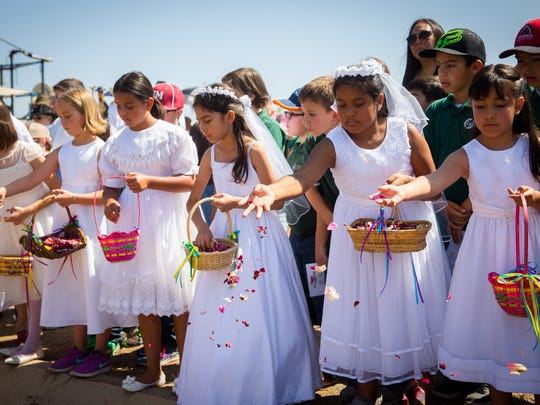 Las Cruces Catholic School students throw rose petals into an acequia during the Blessing of the Fields ceremony at the New Mexico Farm & Ranch Heritage Museum, May 13, 2016.