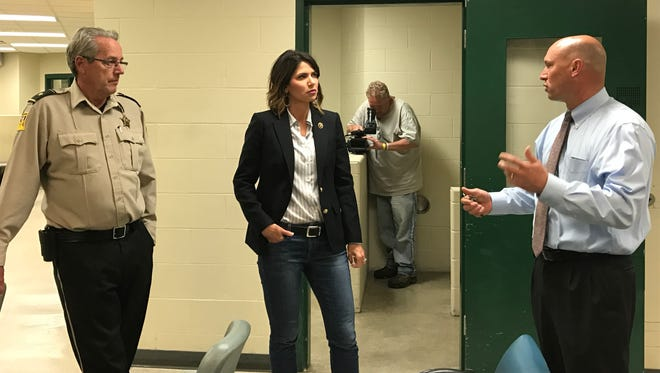 Minnehaha County Sheriff Mike Milstead, left, Rep. Kristi Noem, center and Jeff Gromer, right, discuss conditions at the county jail Thursday.
