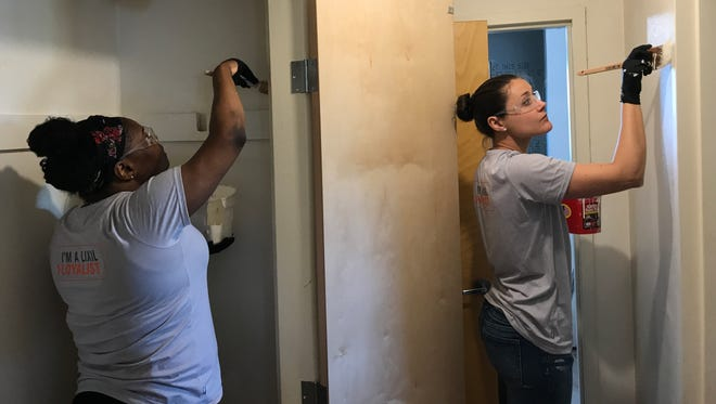Volunteers of Piscataway-headquartered American Standard paint a bedroom in one of the 12 units at Naomi's Way, a permanent housing complex for the homeless run by Catholic Charities Diocese of Metuchen.