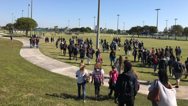 Marjory Stoneman Douglas high school students walk  two miles from their school to memorials set up for the 17 students killed by a gunman on Valentine's Day.