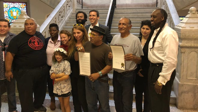 Supporters of recognizing Indigenous Peoples' Day in Cincinnati gather with Councilmembers  P.G. Sittenfeld and Tamaya Dennard in City Hall on Oct. 3, 2018. Guy Jones, president of the Miami Valley Council for Native Americans, third from the left holds the official proclamation.