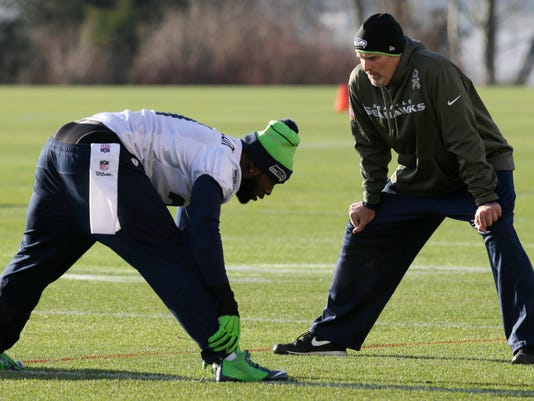 Seattle Seahawks strong safety Kam Chancellor, left, talks with defensive coordinator Dan Quinn, right, during warmups before NFL football practice Wednesday, Jan. 14, 2015 in Renton, Wash. The Seahawks will face the Green Bay Packers Sunday in the NFC Championship game. (AP Photo/Ted S. Warren)