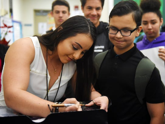 """Recording artist and contestant on the current season of """"The Voice"""", JessLee, signs an autograph for Murray Middle School eighth-grader Brian Baca on Friday, March 9, 2018 while visiting choir and band students. JessLee, who attended Murray Middle School, spoke to the students about chasing their dreams and believing in themselves. """"Life is going to throw struggles at you and put up hurdles,"""" JessLee said, """"but those hurdles are there to make you stronger. You can't have growth without the struggle."""" JessLee will be on Blake Shelton's team on """"The Voice"""" which airs at 8 p.m. Monday and Tuesday on NBC."""