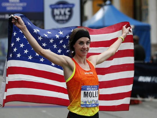 Molly Huddle holds up the flag after her win Sunday.