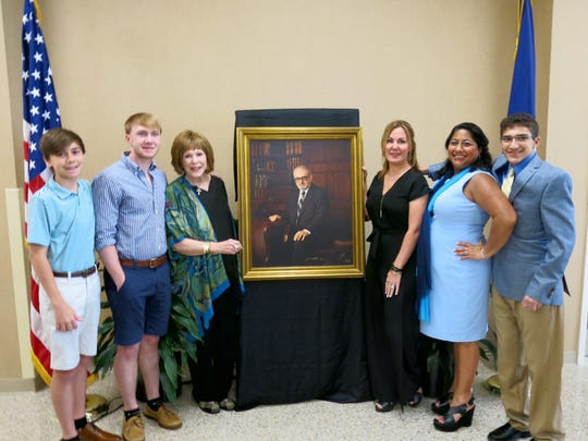 Christopher Sheby, Stanford Shelby, Susan Shelby, Carolyn Shelby, Vicky Shelby, Michael Tola-Godfrey Shelby surround a photo of the late Dr. Stan Shelby at dedication of a Willis-Knighton cardiovascular surgery institute.