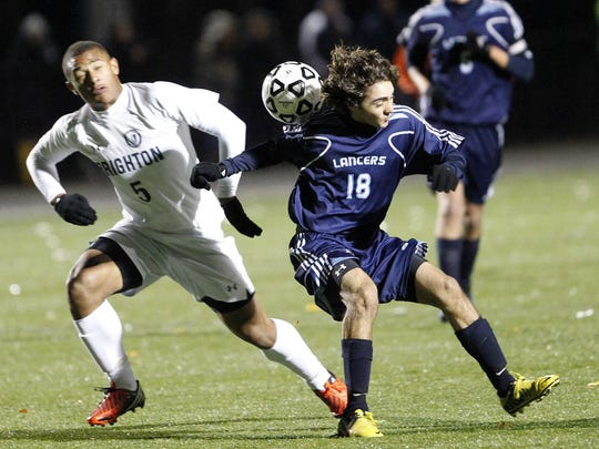 Eastridge's Chaz Aiello, right, positions himself under a ball against Brighton's David Medina during Section V Class A semifinal soccer action on Nov. 1, 2012.