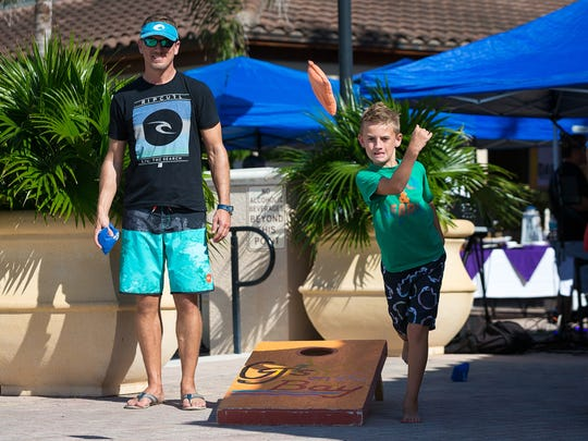 Naples resident Josh Evans plays corn hole with his son, 10-year-old Cameron Evans, at the second annual Marco Island Craft Beer Festival on Sunday, Nov. 6, 2016, on Marco Island.