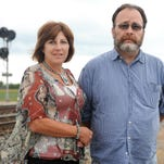 Steve and Nancy Fensch stand in front of a CSX train that has stopped on the tracks blocking the road by their house Wednesday evening.