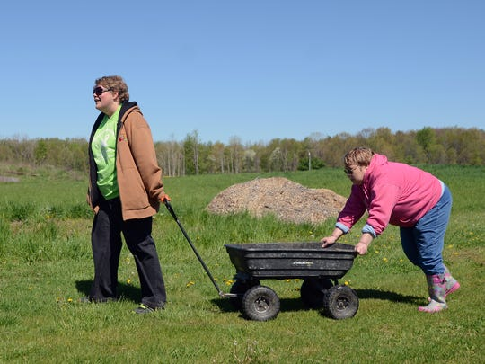Farm workers, Jill Vance, and Sharon Doherty push and pull a cart for stones Monday, May 16, at the Special Dreams Farm in St. Clair.