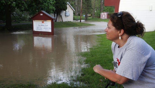 Avon resident Diana Farrell looks at the flood water flowing around the Avon Wesleyan Church at the corner of Spring and Genesee Streets in the village after heavy afternoon rain caused flooding for the second day in a row.