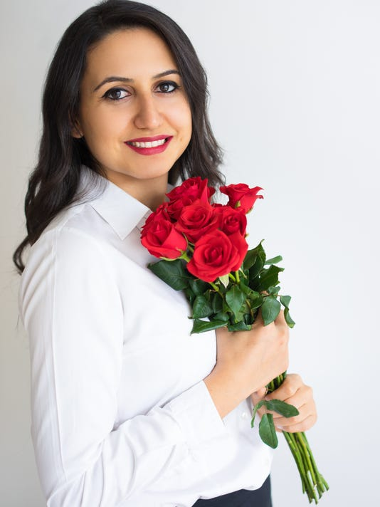 Excited attractive woman holding bouquet