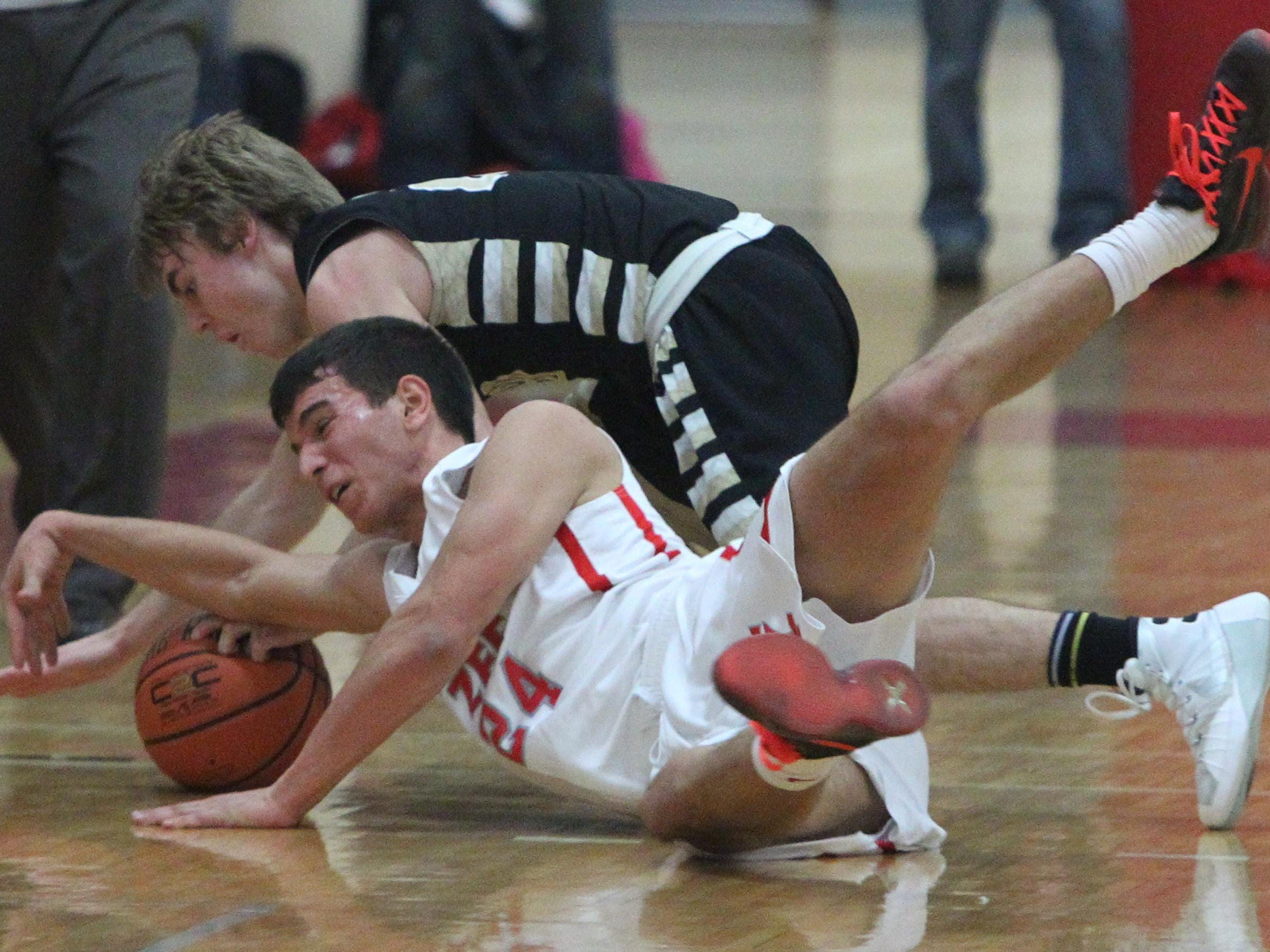 Tappan Zee's Rob McWilliams fights for a loose ball with Nanuet's Terrence Rogers during their game at Tappan Zee Wednesday. Tappan Zee won 59-46.