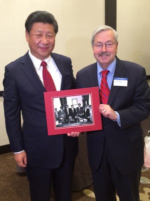 Chinese President Xi Jinping and Gov. Terry Branstad. Branstad on Tuesday held a 1985 photo taken when Xi was part of a Chinese delegation visited the Iowa governor's office in Des Moines. Branstad was serving his first term as governor at the time.