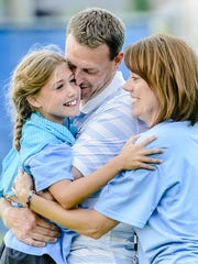Lansing United owner and president Jeremy Sampson (center) gets a hug from his wife, Gena, and daughter, Grace, after United won the NPSL Midwest Regional in 2014. Running a soccer club has been a family endeavor.