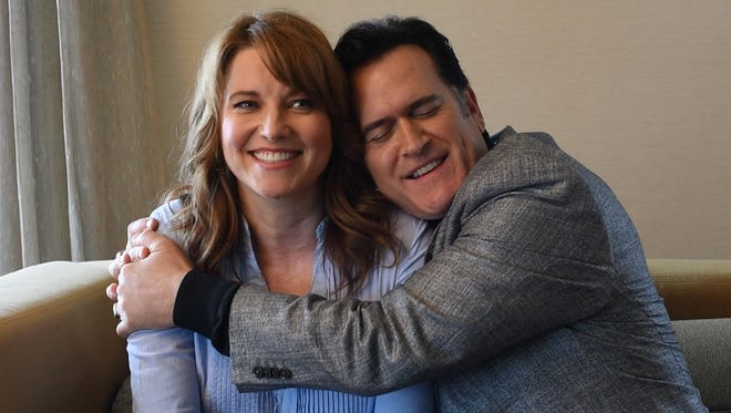 Bruce Campbell, right, hugs his friend and 'Ash vs Evil Dead' co-star Lucy Lawless during an interview with USA TODAY.