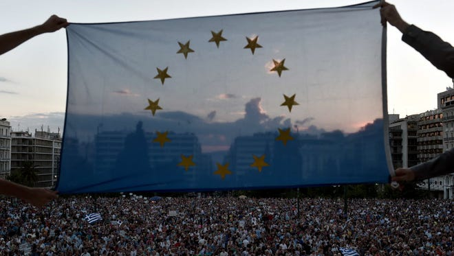 Protesters hold an EU flag during a pro-European demonstration in front of the Greek parliament in Athens on June 18, 2015.