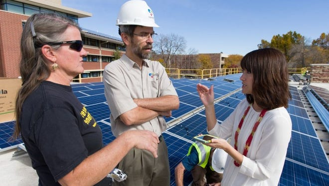 Colorado State University Facilities Engineer Carol Dollard, Namaste Solar Commercial System Designer Rick Coen and CSU Housing and Dining Services Director of Communications Tonie Miyamoto talk about projects as contractors with Namaste Solar install an array of solar panels capable of powering 14 homes on the roof of Colorado State University's Braiden Hall.