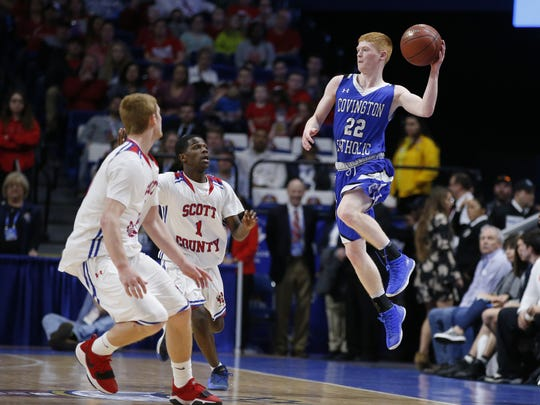 Covington Catholic's Aiden Ruthsatz, 22, right, passes the ball against Scott County's Cooper Robb, left, and Cam Fluker, 1, during the championship game of the Whitaker Bank/KHSAA Boys' Sweet 16 basketball tournament played at Rupp Arena in Lexington, Ky. Sunday March 18, 2018.