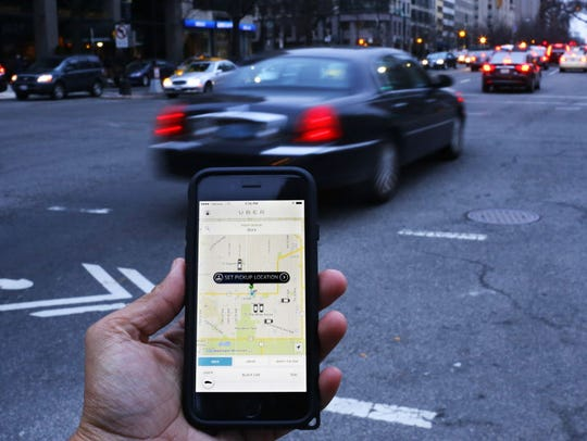 An UBER application is shown as cars drive by in Washington,