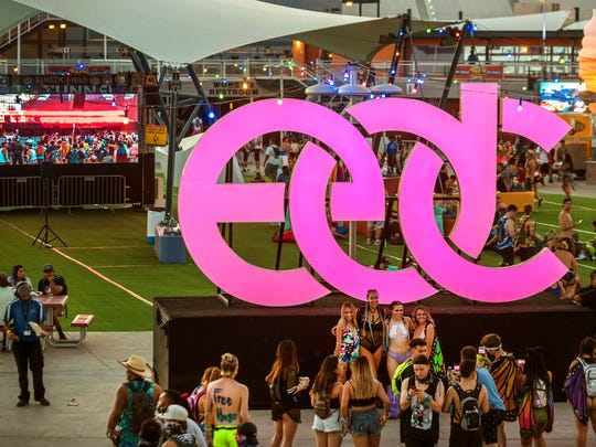 Attendees gather for a pose beneath the giant Electric Daisy Carnival neon sign during the opening night of EDC Las Vegas 2017 at the Las Vegas Motor Speedway in Las Vegas on Friday, June 16, 2017.