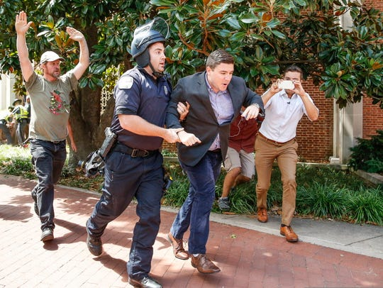 Unite the Right rally organizer Jason Kessler is escorted away from counterprotesters and the Charlottesville City Hall grounds after a news conference on Aug. 13, 2017.