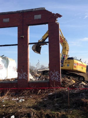 An excavator crew prepares to start demolition of a vacant building on Detroit's west side, Wednesday, Dec. 28, 2016. The building on Cloverdale likely will be the last structure demolished this year under Detroit's expansive blight elimination program.