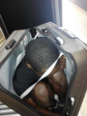 In this photo released by the Spanish Guardia Civil on Tuesday, Jan. 3, 2017, a 19 year-old migrant from Gabon is photographed in a suitcase, in Ceuta, Spain. Border guards have recently detained two Moroccans for attempting to smuggle migrants concealed in a suitcase and in a car as they crossed the border into Ceuta, Spain's enclave in North Africa. Custom officials found a 19 year-old migrant from Gabon hidden in a suitcase pushed on a trolley by a woman who tried to cross the land border from Morocco on December 30, said a spokesman with the Guardia Civil in Ceuta.