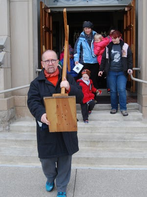 The Rev. Stephen Rooney carries a large cross down the steps of Holy Cross Catholic Church in Marine City at the start of a Good Friday cross walk.