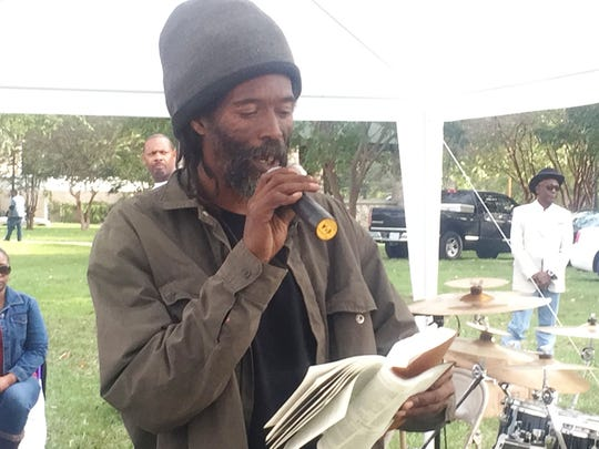 Michael Lewis gives a message at Poindexter Park on Sunday just before members of The Healing Place served a warm lunch to the group of homeless that gather there on Sundays.