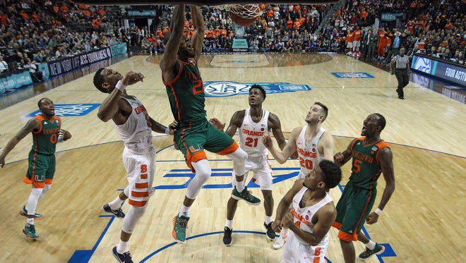 Miami forward Kamari Murphy (21) dunks against Syracuse guard Andrew White III (3) during the second half of an ACC Conference Tournament game at Barclays Center.