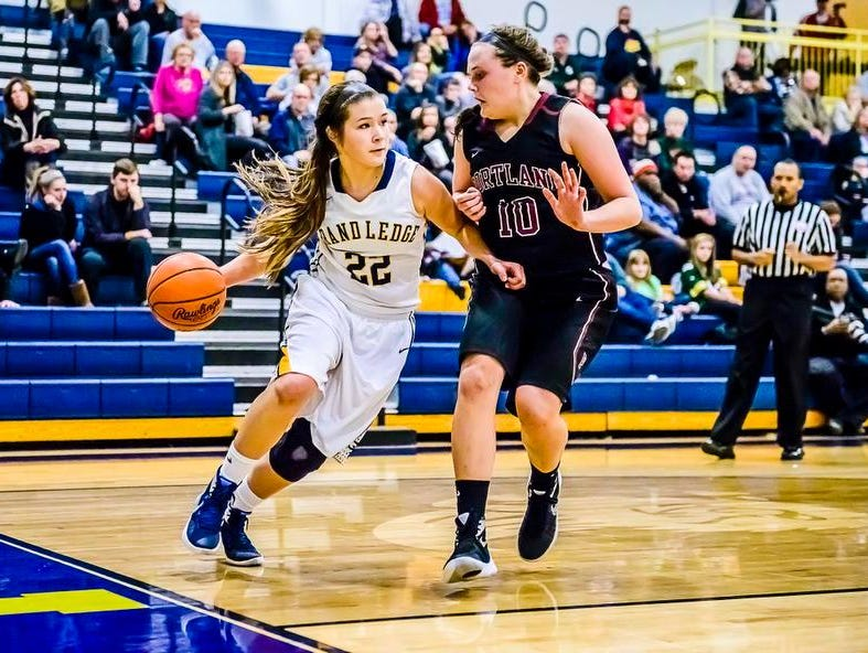 Vanessa Odlum ,left, of Grand Ledge drives the baseline while being defended by Olivia Roe of Portland.