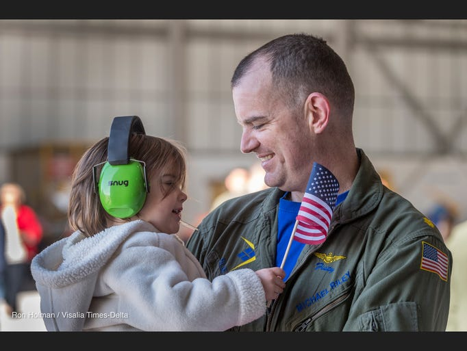 LCDR Michael Riley holds his daughter Gabrielle, 2,