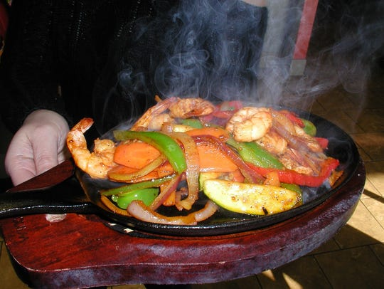 Steam rises from fajitas con camarones which is grilled