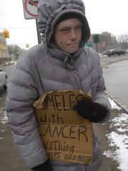 Kirsten, 37, who often panhandles at the corner of Maple and Woodward, says she has stomach cancer and recently lost her husband and her mother.