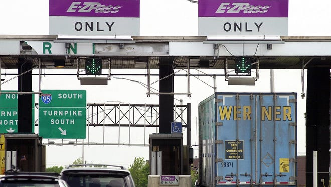 Cars and a truck go through the E-ZPass lanes at Exit 8A of the New Jersey Turnpike in Monroe Township, N.J., on May 12, 2003.