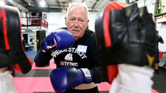 Jim Poff works with his daughter-in-law Melina Poff during a Rock Steady Boxing class on Tuesday, March 28, 2016, at Stevens Family Taekwondo. The class helps Parkinson's patients by providing physical activity and helps strengthen their muscles, and can even slow the progression of the disease.