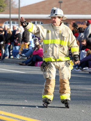 Chief of the Parsonsburg Fire Company, Steve White waves as he skates down Mt Hermon Road during a Salisbury Christmas Parade.