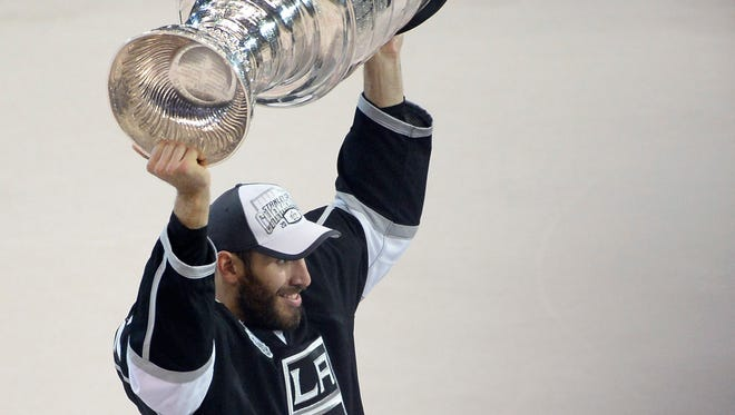 Los Angeles Kings left wing Dwight King hoists the Stanley Cup after defeating the New York Rangers in Game 5 in June.