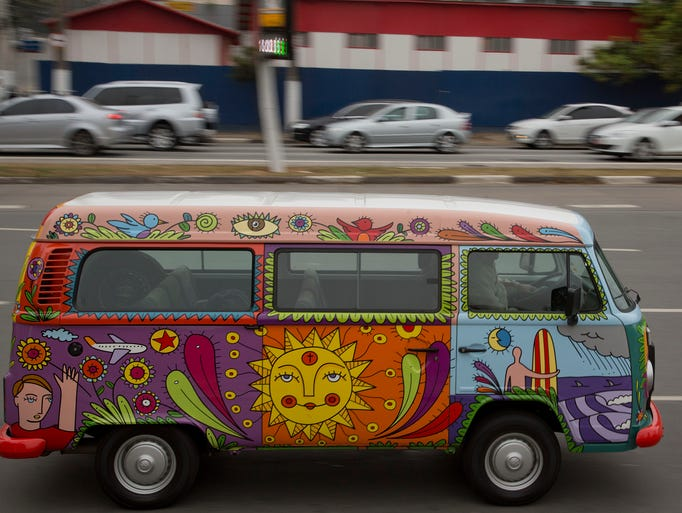 "Advertising executive Marcelo Serpa drives his Volkswagen van, or Kombi, emblazoned with a ""rolling mural,"" that he painted, through the streets of Sao Paulo, Brazil. Production of the bus is about to end."