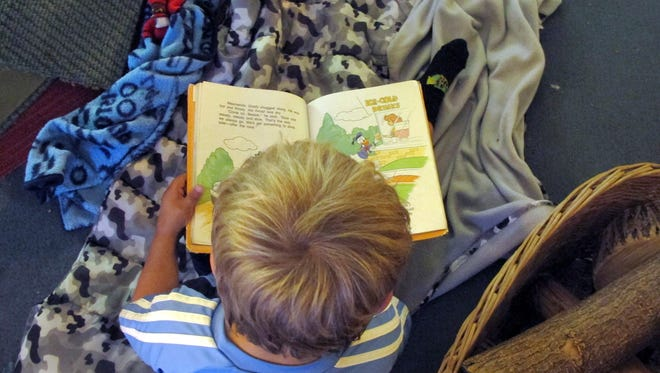 In this July 7, 2016, photo, one of the children at Annette's Preschool reads a book in Hinesburg. Vermont has become the first state to extend publicly funded pre-kindergarten programs to all 3-year-olds as of this month.
