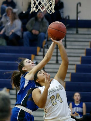Pittsford Sutherland's Hannah Catallo-Stooks jumps with he ball as Batavia's Ryann Stefaniak reaches for it in the third quarter at Pittsford Sutherland High School.