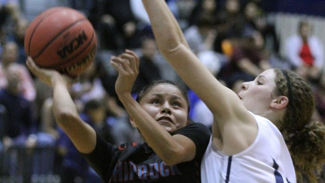Shiprock's Melanie Secody, left, shoots while being defended by Piedra Vista's Dani Russo on Dec. 20 at the Jerry A. Conner Fieldhouse in Farmington.