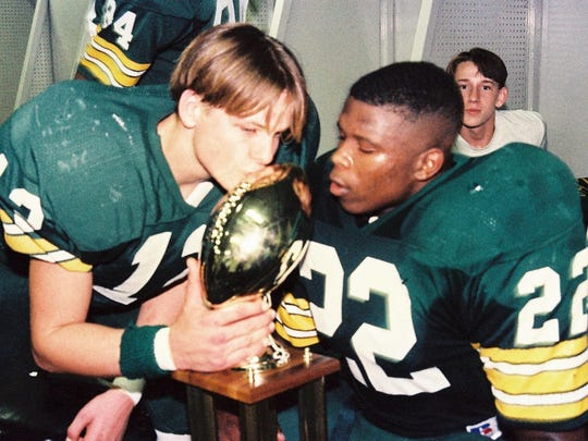 Cecilia High's Beau Guidry (12) and Jermaine Davis (22) take turns kissing the Class 3A state championship trophy for the Bulldogs back in 1995.